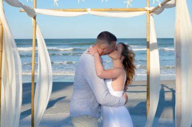 Couple kisses at beach elopement ceremony