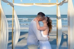 Couple kisses at beach elopement ceremony
