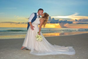 A bride and groom share a kiss as the sunsets at their wedding in Siesta Key, Florida.