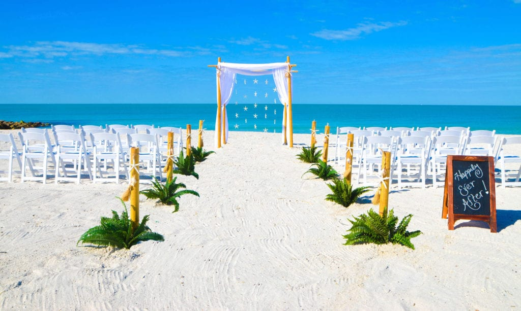 A starfish beach wedding ceremony canopy and aisle way on the beach in Florida.