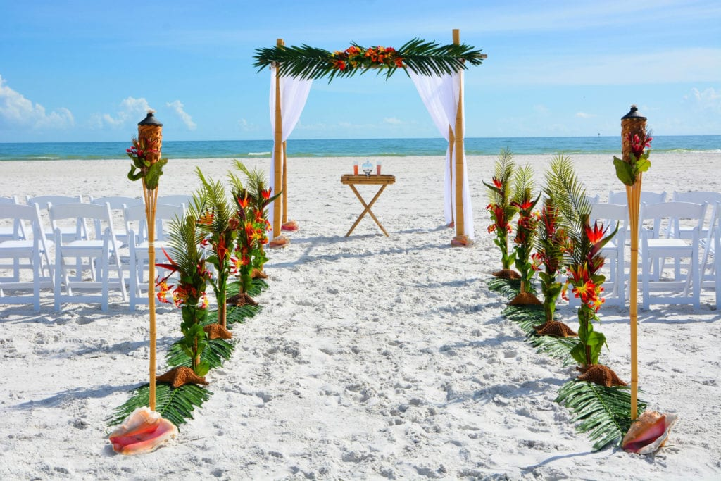 Tropical Florida Beach Wedding arch with conch shells, tiki, greenery