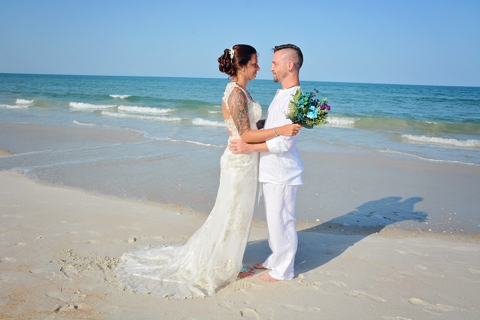Butler Beach wedding couple embraces by ocean