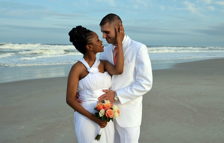 Couple embraces after wedding on Daytona Beach at sundown