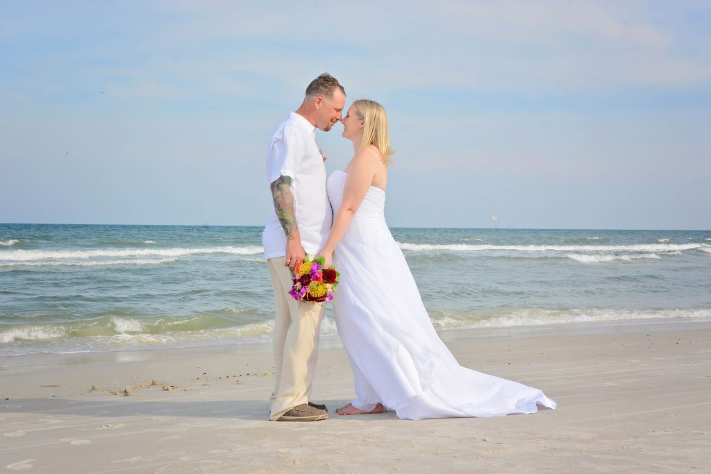 Couple gazes together by St. Augustine ocean after beach wedding