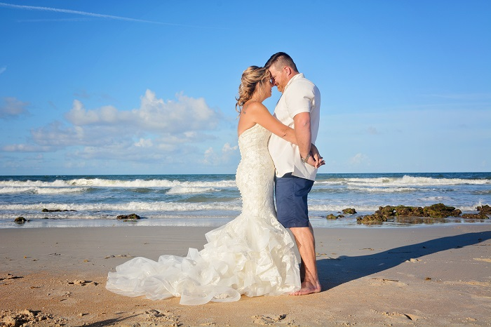 Bride and groom hug at Palm Coast Beach wedding by the sea