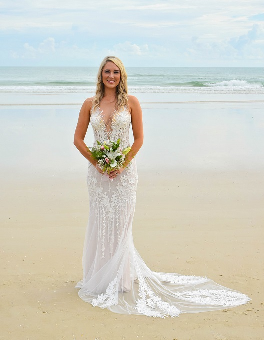 Simple white wedding gown with straps on bride in Siesta Key