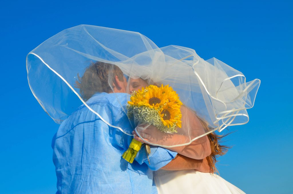 Bride carries sunflowers on the beach in Florida and hugs groom