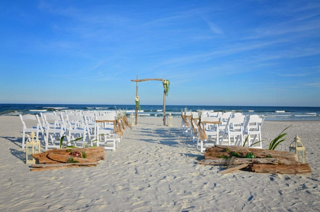 Driftwood wedding arch on the beach with white chairs