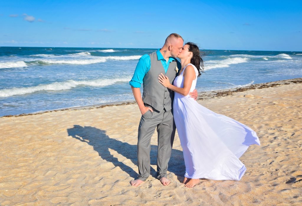 Couple kissing on St Augustine beach after wedding