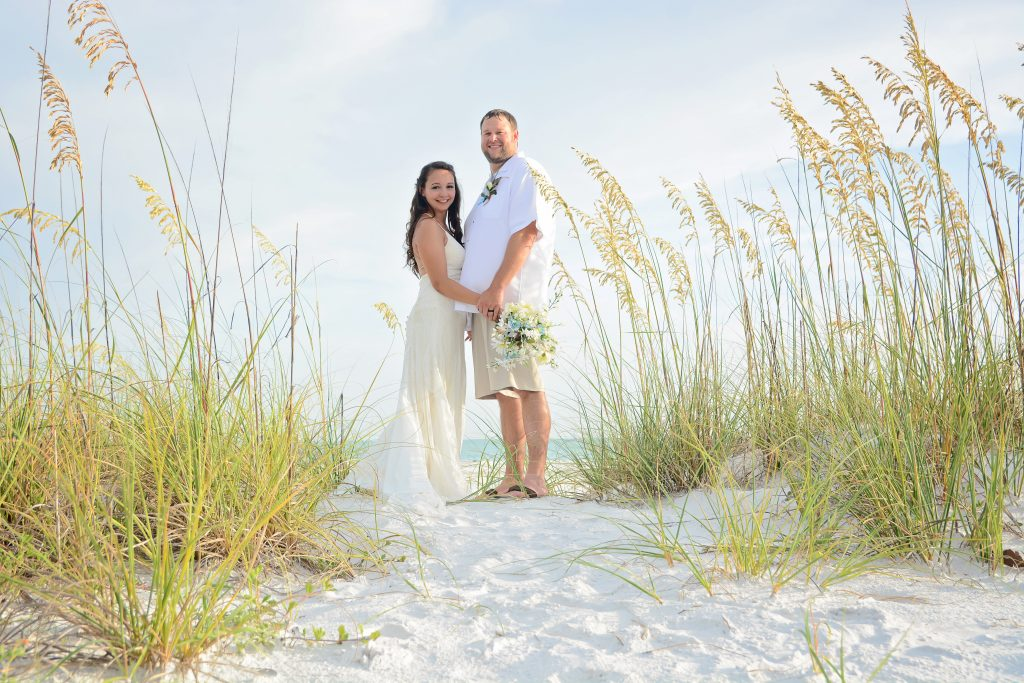 Siesta Key wedding couple hugging in sea oats on beach