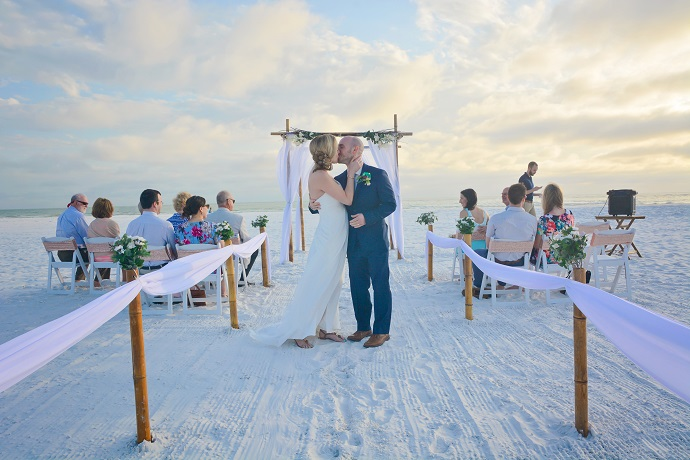 Couple kisses at Siesta Key beach wedding at sunset under bamboo arch