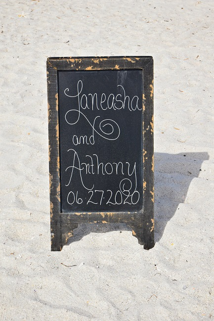 Chalkboard sign announcing couple beach wedding vows