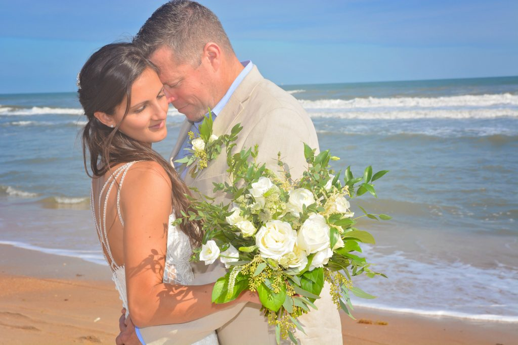 Bride with white rose bouquet and groom hug on st augustinebeach