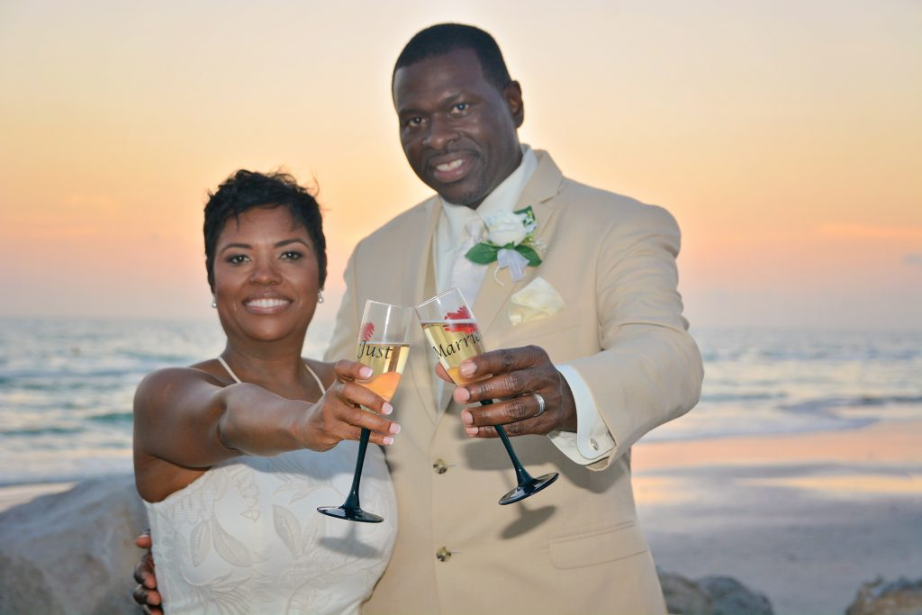Wedding couple on the beach with toasting glasses