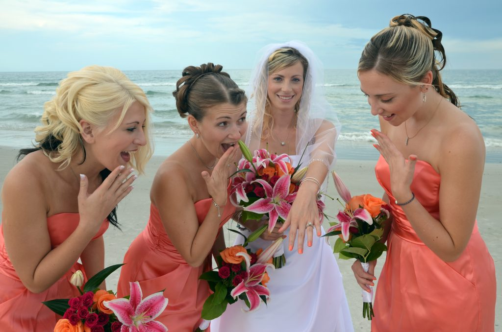 Bridesmaids funny faces on beach with bride by ocean