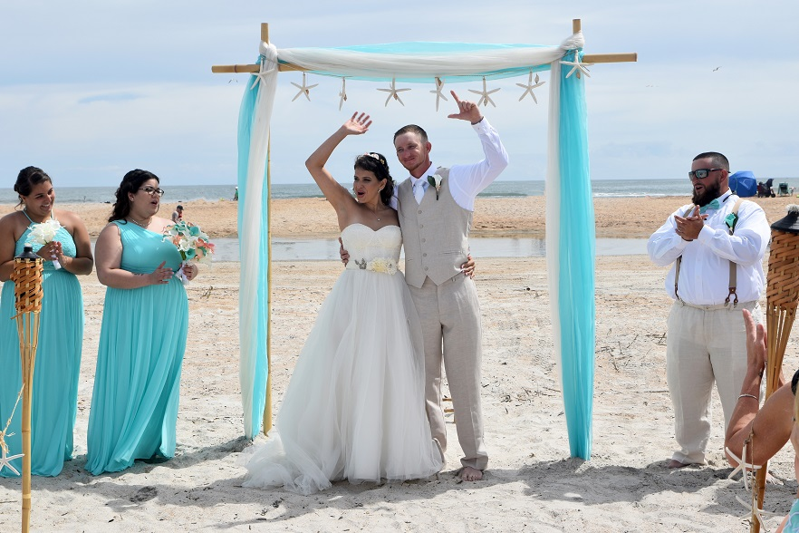 Beach wedding couple cheers underneath teal fabric arch