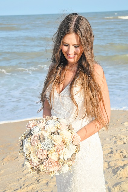 Bride looking down at bouquet on Anastasia Island Beach FL