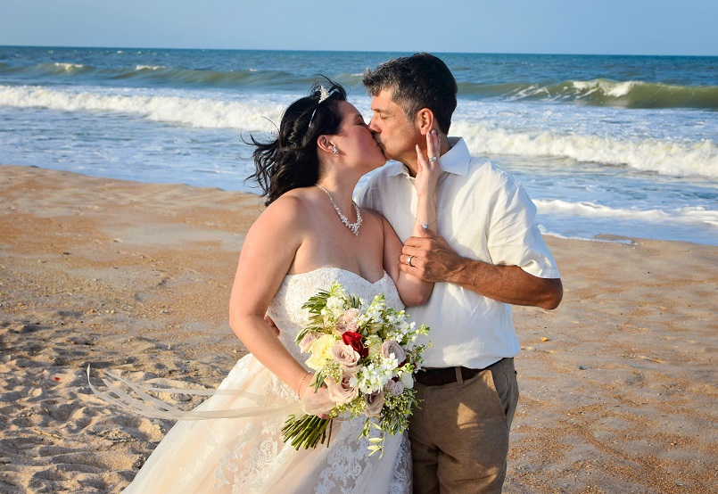 Couple kisses by ocean in St. Augustine at beach wedding