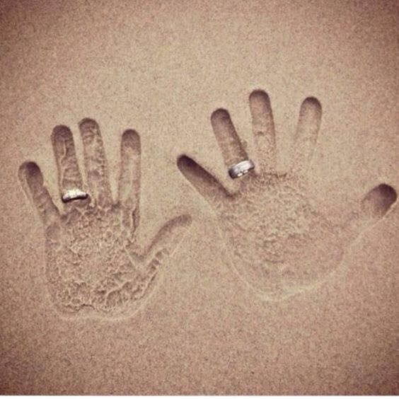 Hands with wedding rings in sand on the beach