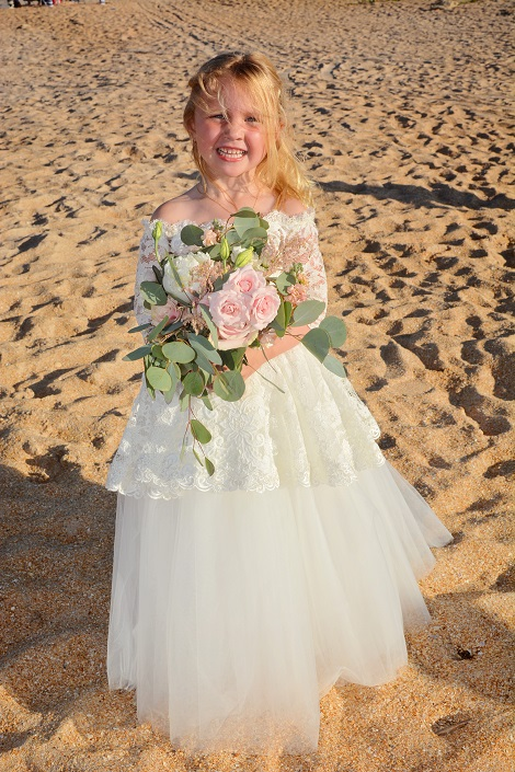 Flower girl on St. Augustine Beach holding flowers