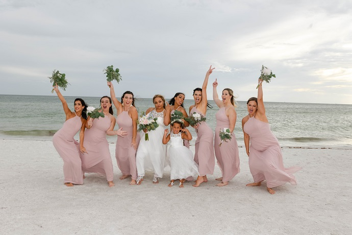 Flower girl and bridesmaids pose in pink dresses on Siesta Key beach