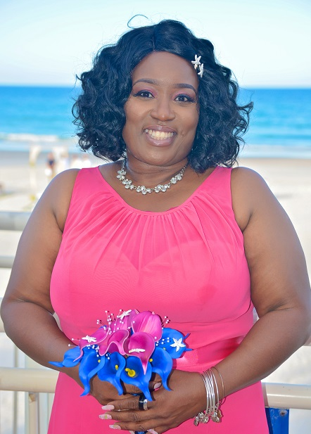 African American bridesmaid holding flowers at beach wedding