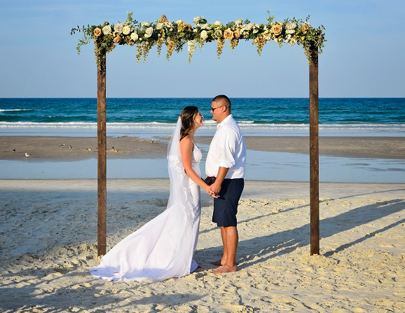 Bride and Groom under wedding arch on Daytona Beach