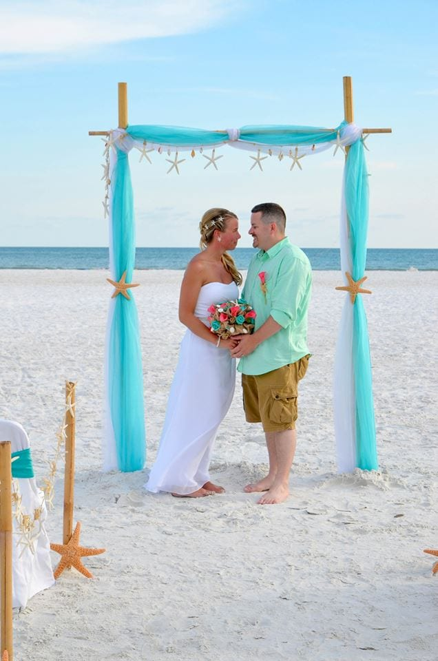 Couple under wedding arch on Fort De Soto Beach