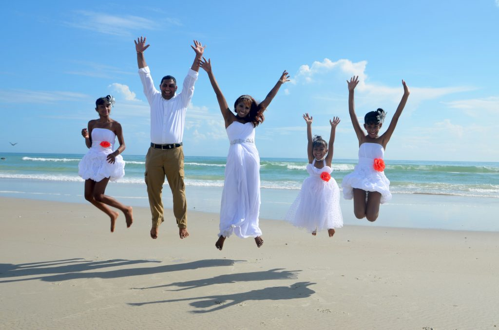 Bridal family jumping on sand in Daytona Beach