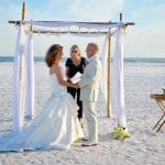 A bride and groom hold hands as they get married in the sand during our Florida Beach Elopements.