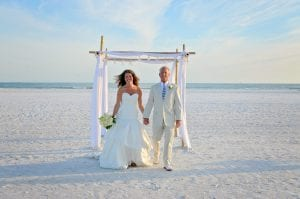 A bride and groom walk away from their ceremony down the aisle after one of our Florida Beach elopements.