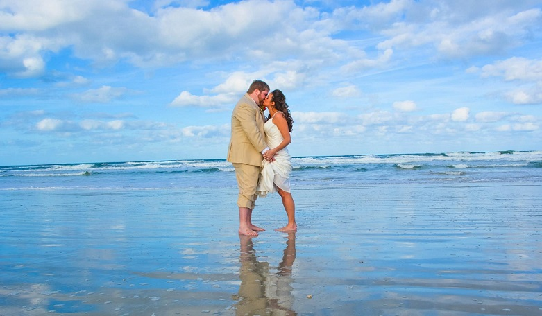 Wedding couple kisses in the surf of the Atlantic in Daytona Beach