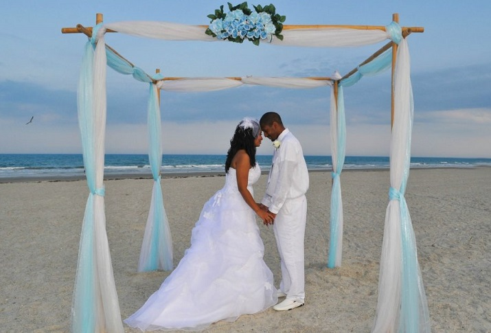 Couple holds hands under blue and white bamboo wedding arch in Cocoa Beach