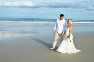 A bride and groom take a stroll during their Daytona Beach Weddings Ceremony.