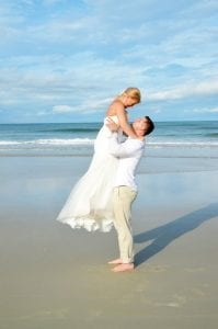 A groom lifts his bride after their Daytona Beach Weddings.