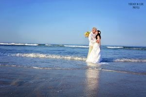 A bride and groom dip their feet in the water during their Daytona Beach Weddings Ceremony photo session.