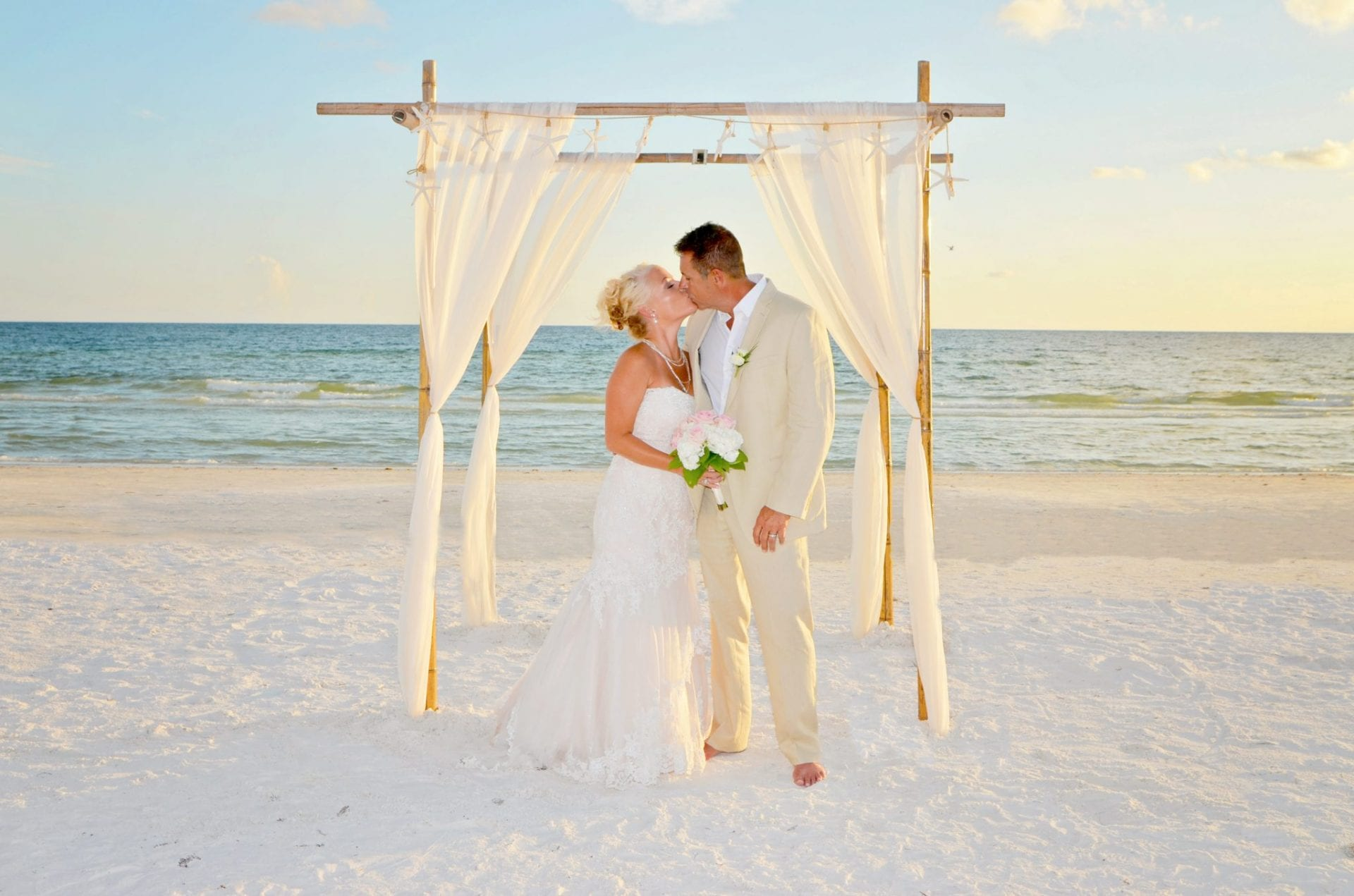 This bride and groom enjoy their Florida Beach Elopements while sharing a kiss under the bamboo canopy.
