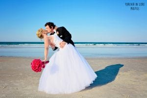 Daytona Beach Weddings are a thing to celebrate. This groom celebrates by dipping his bride by the ocean.