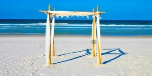 Our Florida Beach Elopements are complete with a bamboo canopy draped in ivory material and a string of starfish across the top.