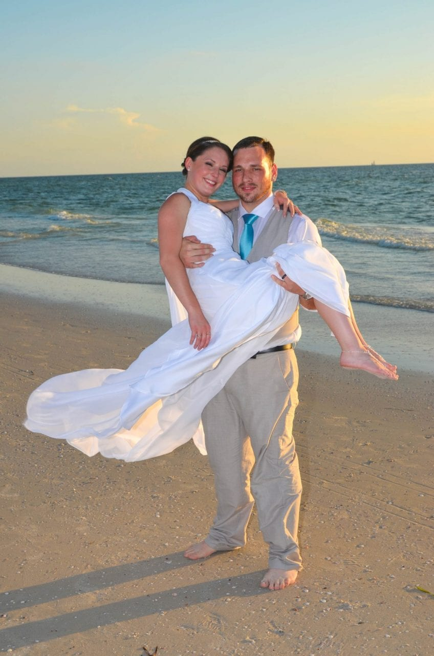 Groom picks up bride after sunset beach wedding in Florida