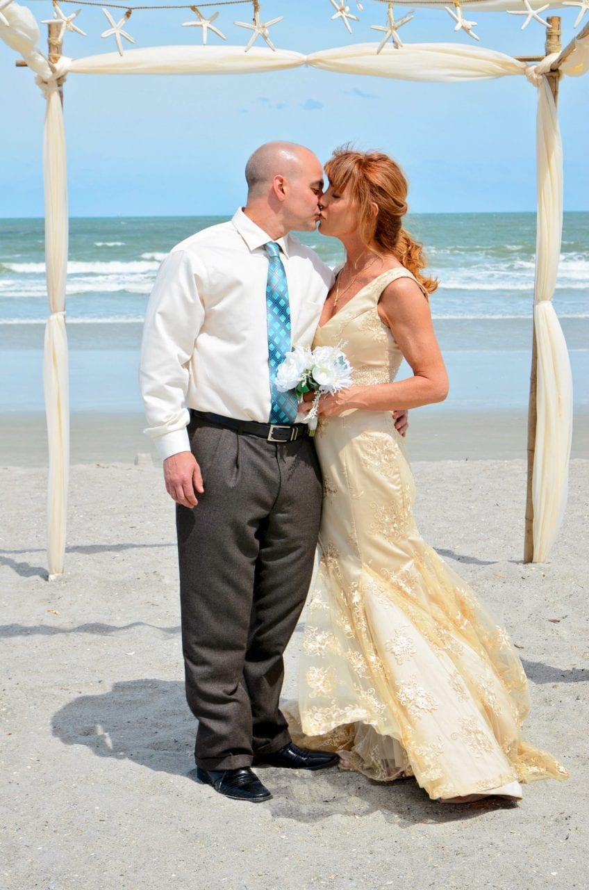 Couple kissing under beach wedding arch with starfish
