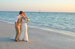 A bride and groom stroll the beach and share a kiss during one of our Clearwater Beach Weddings.