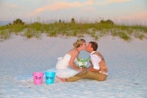 A bride and groom share a kiss in the dunes after one of our Clearwater Beach Weddings.