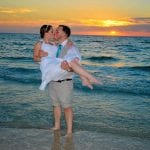 A groom holds a bride in the ocean during one of our sunset Clearwater beach weddings.