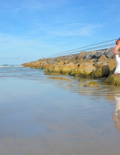 Couple kisses on jetty for beach wedding photos