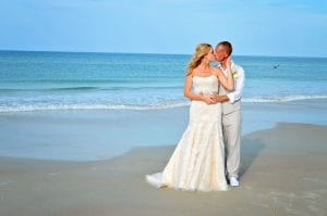 A bride and groom stand in the sand during one of our Daytona Beach Weddings.