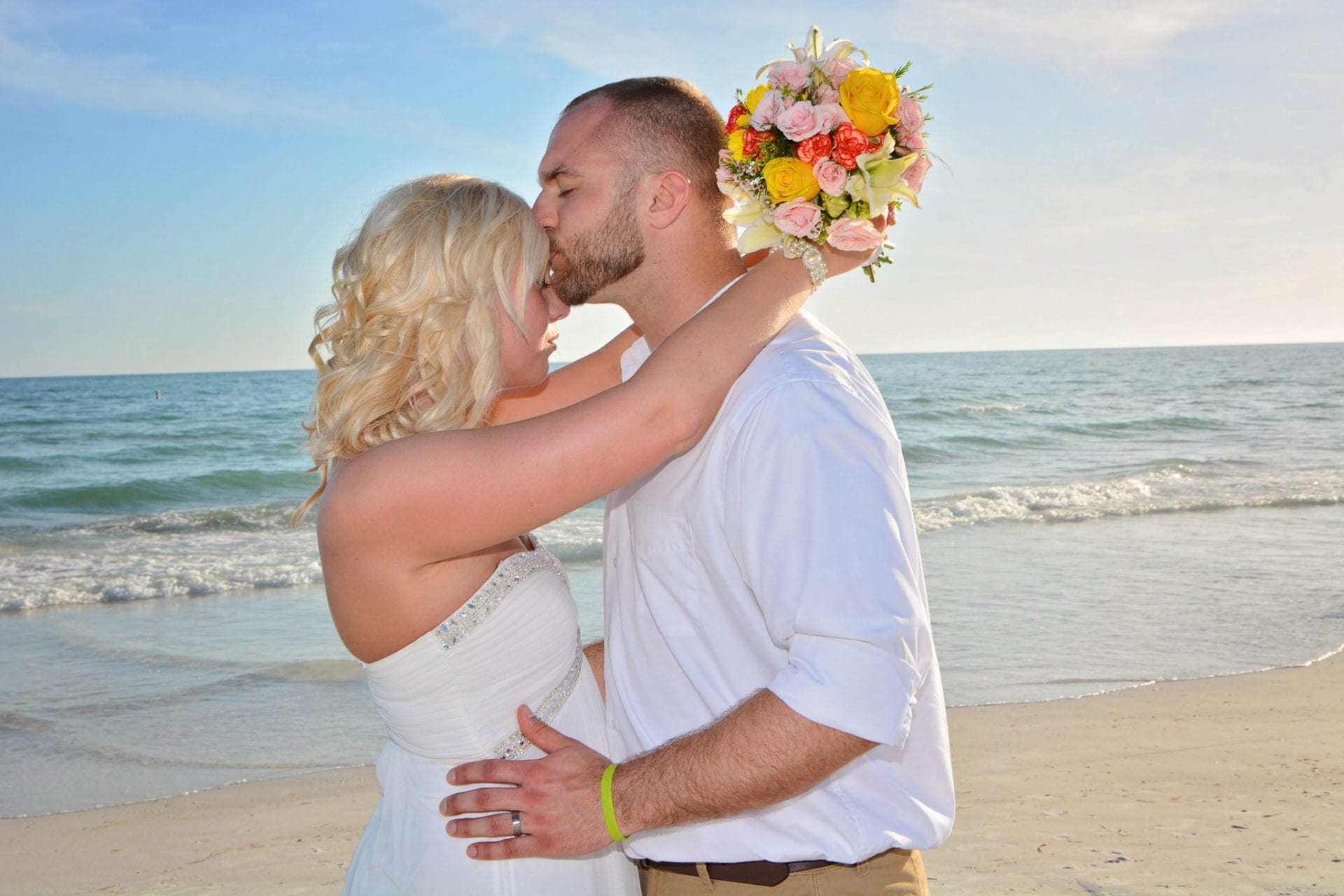Our Siesta Key beach Weddings include these beautiful photographs of a groom kissing the brides forehead.