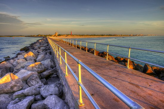 Ponce Inlet Beach jetty walkway at sunset with view of lighthouse