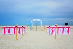 White covered chairs with fusia sashes are featured in one of our Destination Weddings in Florida.