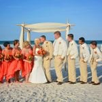 Destination Weddings in Florida show off this bride and grooms kiss while the wedding party overlooks.